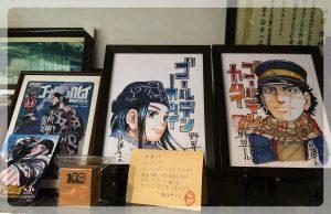Kaizawoilla oli työhuoneessaan esillä Golden Kamuy -kuvistusta omistuskirjoituksella.